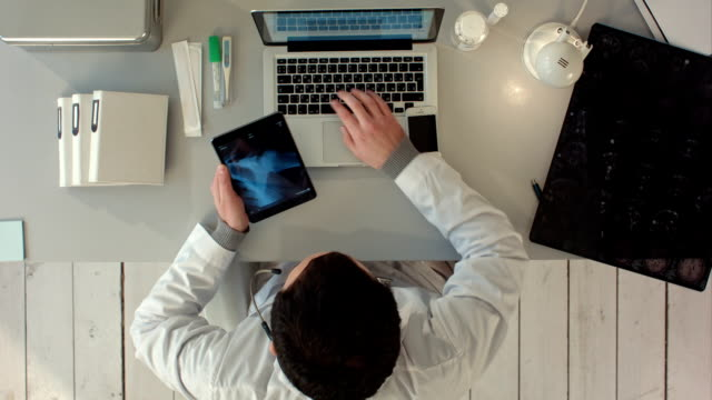 Man using tablet pc against medical xray. Top view video
