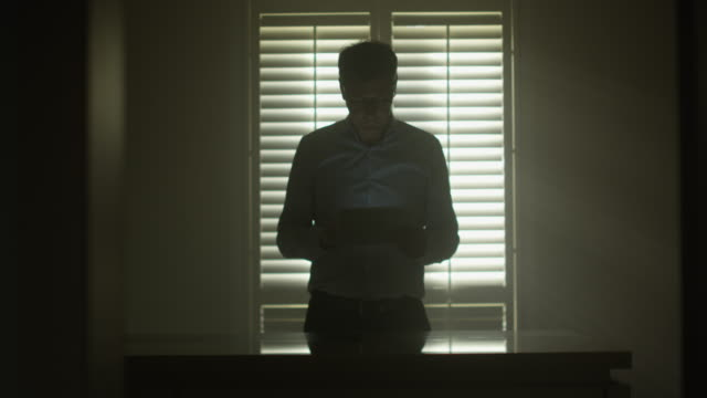 Man using tablet Man standing in front of window shutters in a dark mood and using a tablet padding stock videos & royalty-free footage
