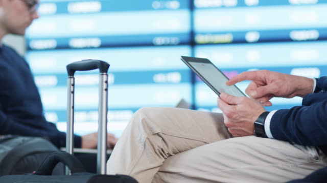 Man using Tablet while Waiting Boarding at Departure Lounge at the Airport. video