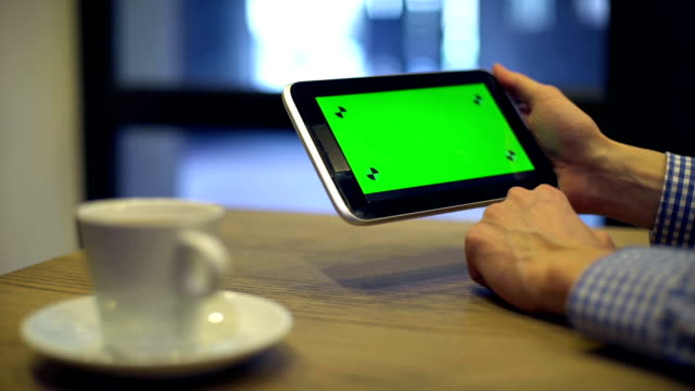 Man using Tablet with Green Screen in coffee house