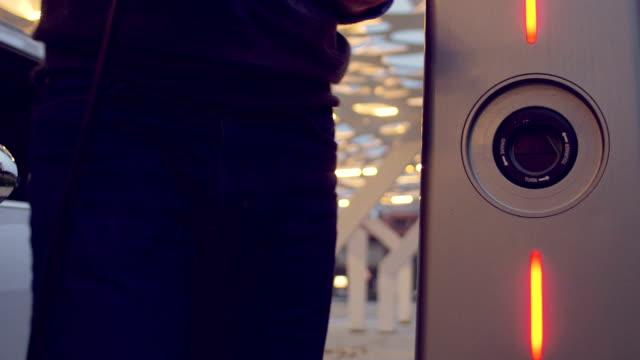 その電気自動車を充電しながらスマート フォンを使用している人 - 電気自動車点の映像素材/bロール