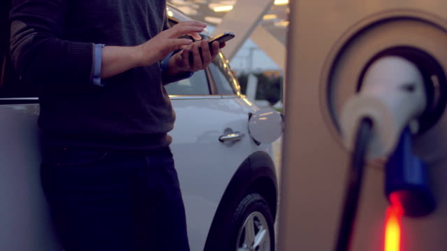man using the smartphone while charging its electric car - carica elettricità video stock e b–roll