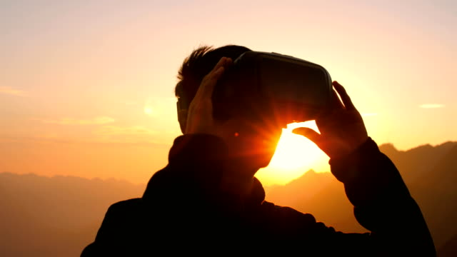 Man using virtual reality headset with mountain sunset background Man using virtual reality headset with mountain sunset background hands free device stock videos & royalty-free footage