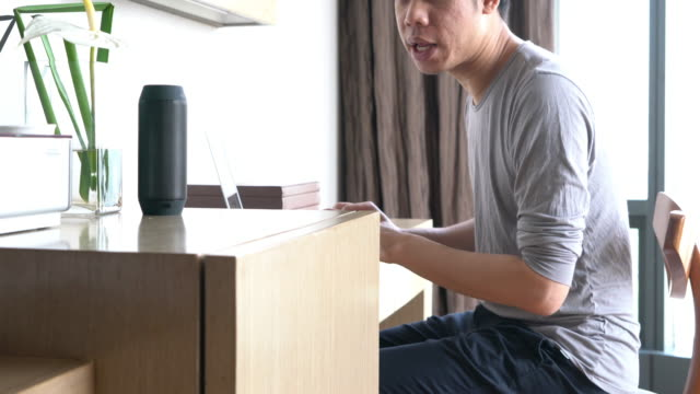 man using voice to command home appliance and equipment - ассистент стоковые видео и кадры b-roll