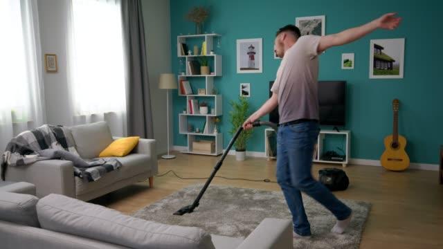 A man vacuums a cozy apartment and dances fun video