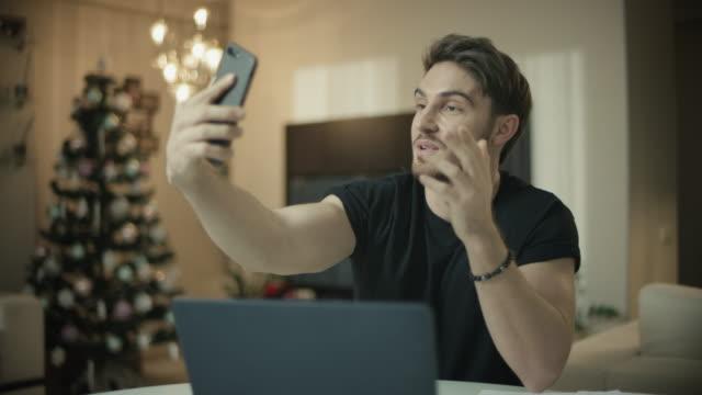 videochiamata dell'uomo sul cellulare a casa di natale. persona maschile che usa la conversazione facetime - christmas movie video stock e b–roll