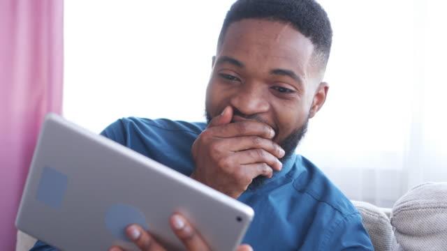 mann video-conferencing auf digital-tablette - junger mann stock-videos und b-roll-filmmaterial