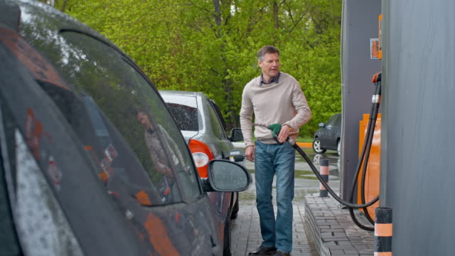 Man Visiting Gas Station Man filling his car at gas pump and then putting back fueling nozzle and sitting into his car refueling stock videos & royalty-free footage