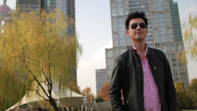 mann wartet seine freundin im park - sonnenbrille stock-videos und b-roll-filmmaterial