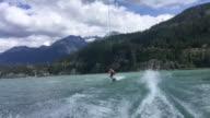 istock Man wakeboards behind motorboat, on mountain lake 1216678632