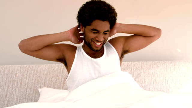 uomo svegliarsi e stretching a letto - ritemprarsi video stock e b–roll