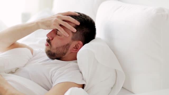vídeos y material grabado en eventos de stock de hombre despierta en la cama en casa - crudo