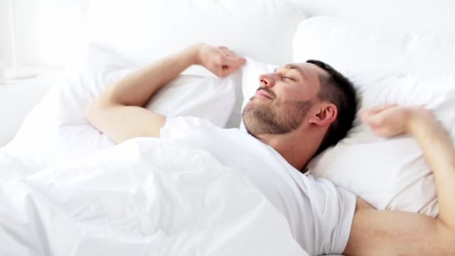 man waking up in bed at home