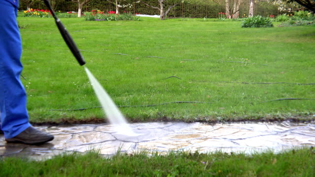 Man walk and wash path with water pressure tool in garden. video
