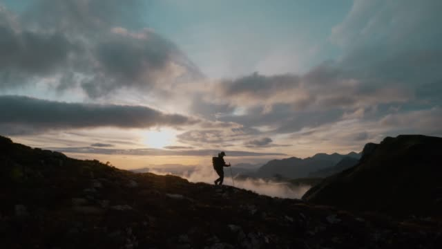 Man walk on edge of epic cliff at sunset in clouds