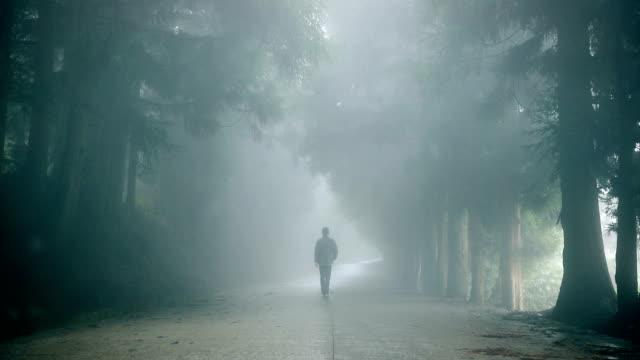 Man walking alone on foggy road