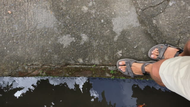 A man walking along a water canal in the Ubud village on the Bali island. Shot on a phone