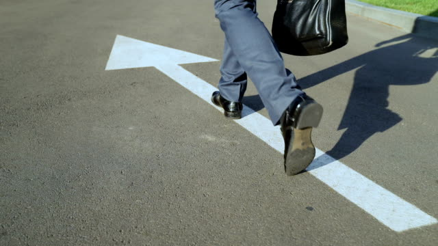 man walking along white arrow, person choosing own life path, going right way - пешеходная дорожка путь сообщения стоковые видео и кадры b-roll