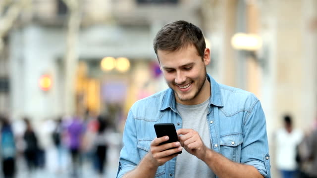 Man walking and using a smart phone in the street
