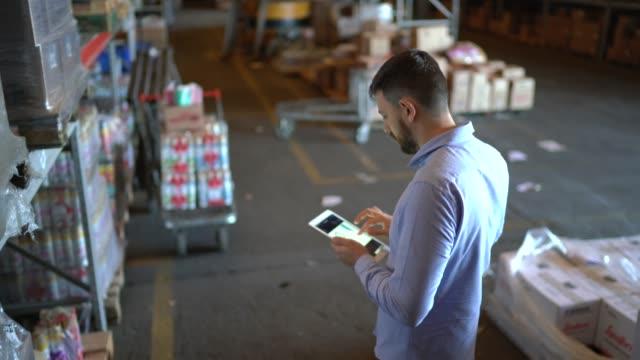 Man walking and using digital tablet at warehouse