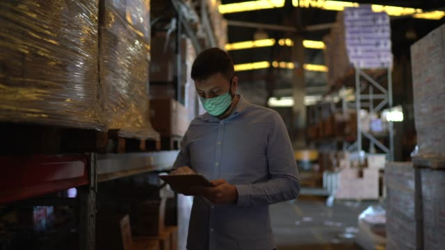 man walking and using digital tablet at warehouse - with face mask - businessman covid mask video stock e b–roll