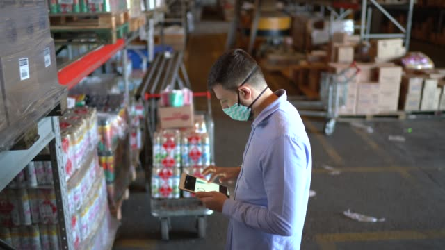 man walking and using digital tablet at warehouse - with face mask - prodotti supermercato video stock e b–roll