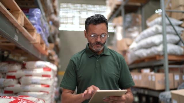 man går och använder sin tablett arbetar i lager/industri - kroppsarbetare bildbanksvideor och videomaterial från bakom kulisserna
