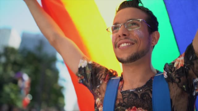 Man walking and waving rainbow flag during LGBTQI parade Man walking and waving rainbow flag during LGBTQI parade gay man stock videos & royalty-free footage