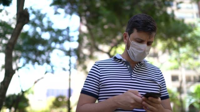 mann zu fuß im park mit handy - tragen gesichtsmaske - smartphone mit corona app stock-videos und b-roll-filmmaterial