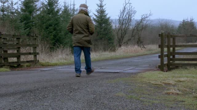 Man walking away from camera on a rural Scottish road 4K footage shot at 50fps and interpreted at 25fps to give a slower motion galloway scotland stock videos & royalty-free footage