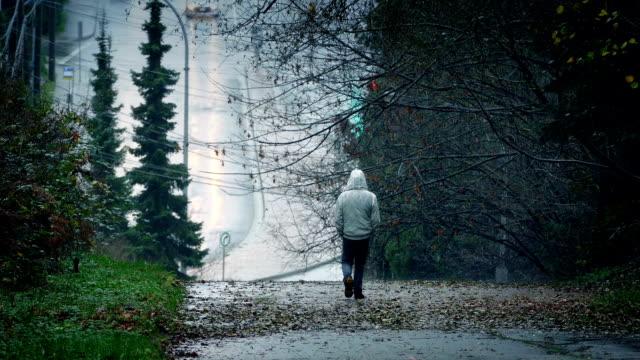 vídeos de stock, filmes e b-roll de homem andando de down hill em dia chuvoso - largo descrição geral