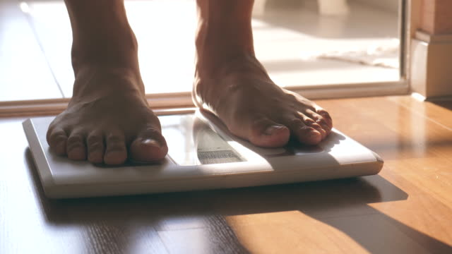 vídeos de stock, filmes e b-roll de homem andando em escala de pesagem corporal - alimentação não saudável