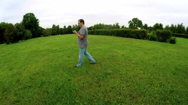 man walking in the park holding smartphone - google стоковые видео и кадры b-roll