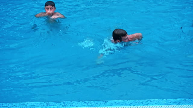 Man walking in the swimming pool on sunny day