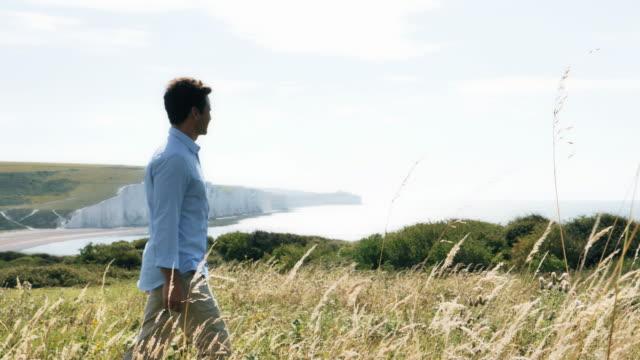 mann geht von links nach rechts. schöne lage an der küste. (1) langsam mo. ws. - introspektion stock-videos und b-roll-filmmaterial