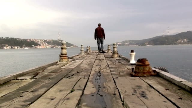Man walking on a wooden pier in cloudy day
