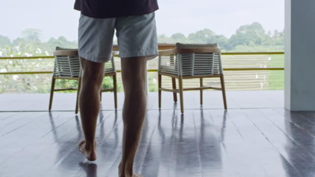 vídeos y material grabado en eventos de stock de hombre caminando en el balcón después de levantarse - imperfección