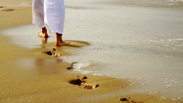 Man Walking on Beach Footsteps Covered by water HD video