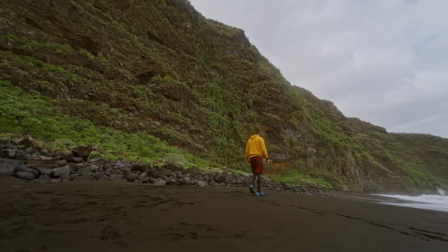SLO MO WS Man walking on black sandy beach / Canary Islands, Spain