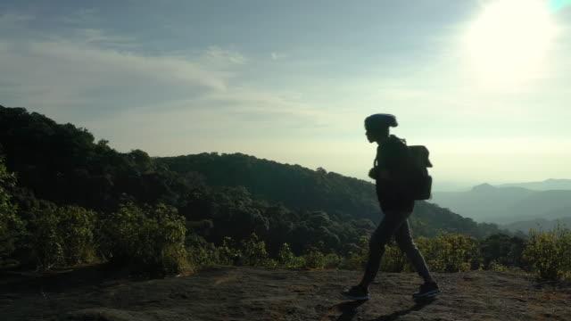 Man walking on mountain peak in silhouette shot