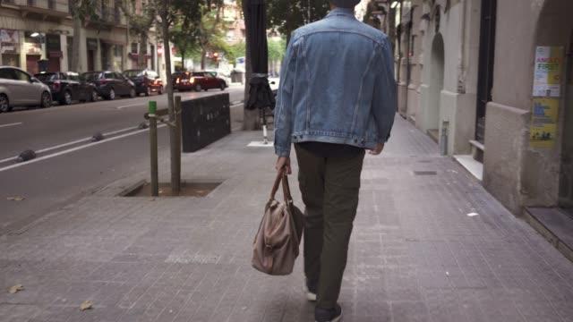 man går på trottoaren av stadsgatan bärväska - människorygg bildbanksvideor och videomaterial från bakom kulisserna
