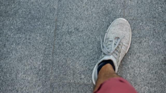 stockvideo's en b-roll-footage met man lopen op de weg. bovenaanzicht van de benen. - running shoes