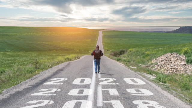 man walking on the road with writing number 2020 - proiezione effetto luminoso video stock e b–roll