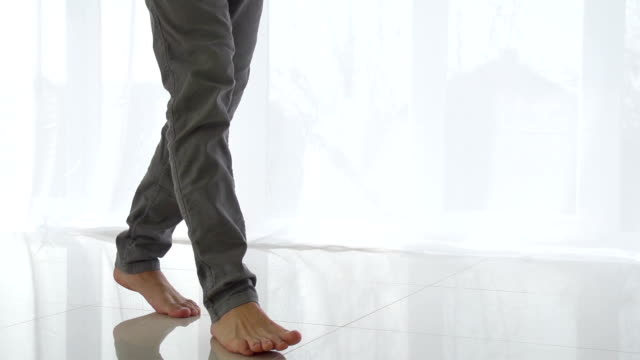 uomo a piedi sul pavimento di piastrelle bianca - scalzo video stock e b–roll