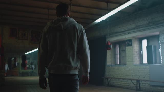 Man walking through boxing gym Athletic man walking through a old boxing gym. Its first dark then the lights are switched on. He stops in front of a punshing bag ready for training. sportsperson stock videos & royalty-free footage