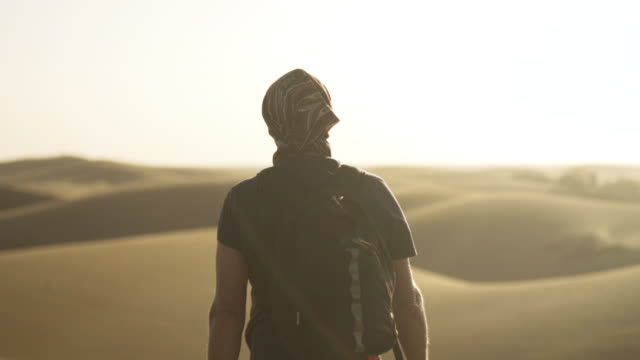 Man Walking Through Sunlit Desert Slow Motion Medium Tracking Shot Of Man With Headscarf And Backpack Walking Through Sunlit Desert Landscape, Rear View extreme terrain stock videos & royalty-free footage
