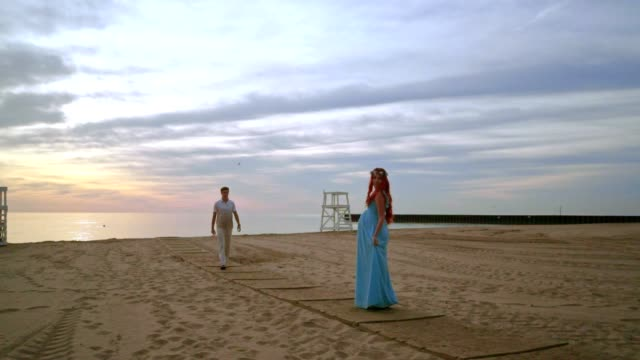 Man walking towards his pregnant wife. Romantic photo session on beach