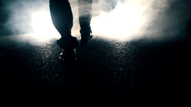 Man walking towards light at night Man walking towards light crime scene stock videos & royalty-free footage