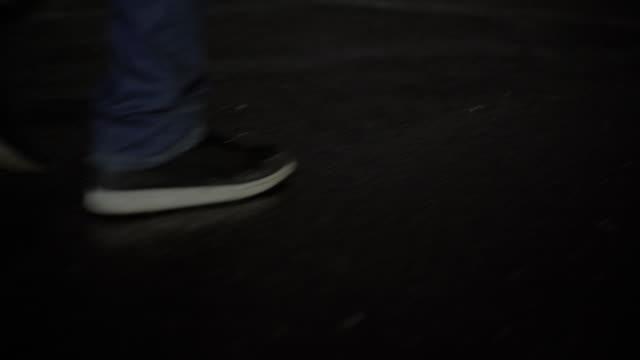 Mann zu Fuß in Richtung Skyline im Regen in der Nacht – Video