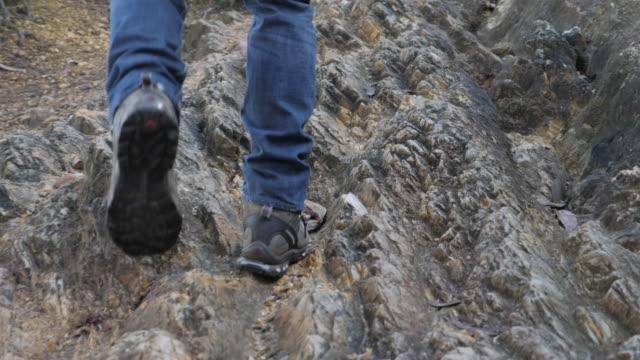 vidéos et rushes de homme marchant dans le sentier de montagne rocheuse - paysage extrême